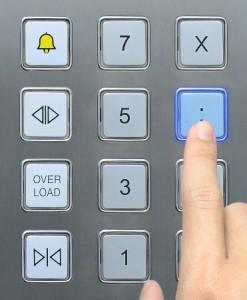 Dito che preme sulla pulsantiera di un ascensore